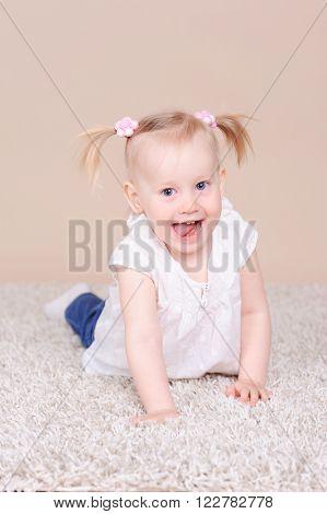 Smiling baby girl 2-3 year old lying on floor. Childhood. Playful.