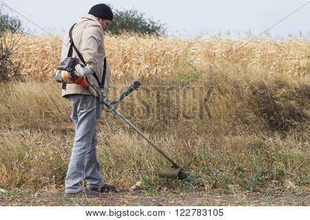DIKANKA UKRAINE - SEPTEMBER 30 2015: Country farmer working mows dry grass trimmer in garden closeup