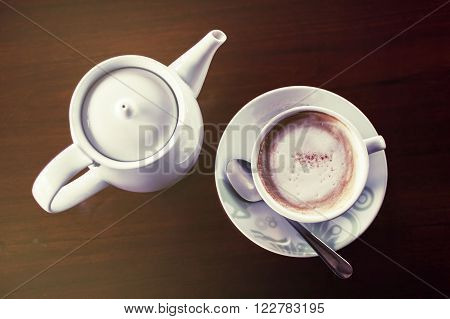 Cup of coffee with hot tea pot on a dark wooden background Vintage tone