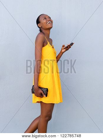 Cheerful African Woman Walking With Mobile Phone