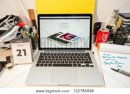 PARIS FRANCE - MARCH 21 2016: Apple Computers website on MacBook Pro Retina in a geek creative room environment showcasing the newly announced iPad pro next to old iPad pro