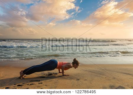 Beautiful sporty fit woman practices Ashtanga Vinyasa yoga Surya Namaskar Sun Salutation asana Chaturanga Dandasana - four-limbed staff pose at the beach on sunset