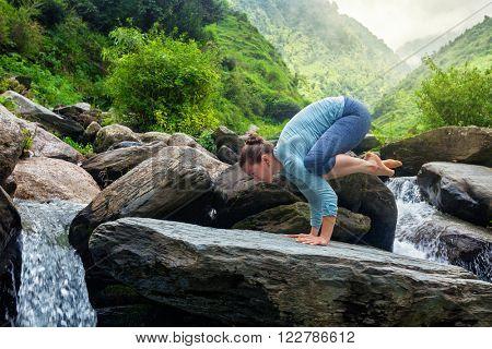 Woman doing Bakasana asana crane pose arm balance outdoors at waterfall