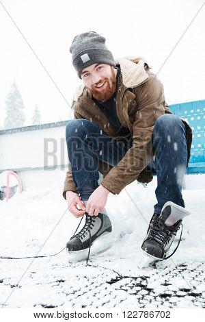 Happy man tying shoelace on ice skates outdoors