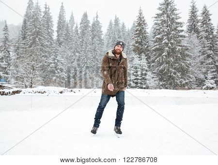 Young man ice skating outdoors with snow on background