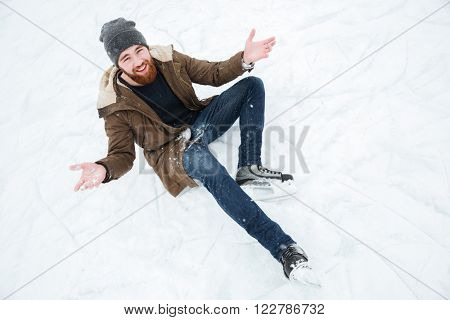 Funny man sitting on the snow in ice skates