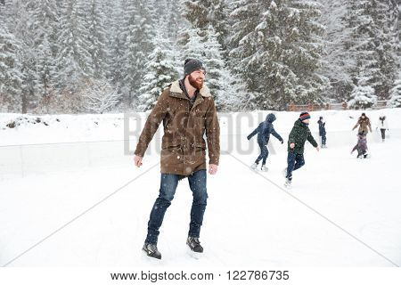 Portrait of a happy man ice skating outdoors