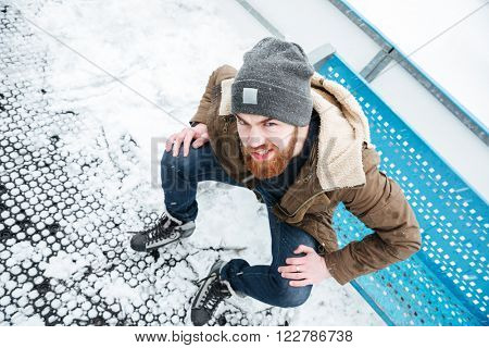 Funny man in ice skates sitting on the bench outdoors and looking at camera