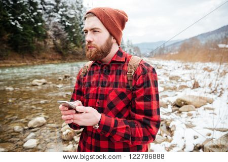 Thoughtful male hiker holding smartphone with river on background