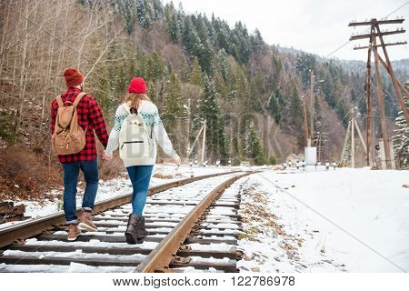Bak view portrait of a couple walking on railway with forest on background