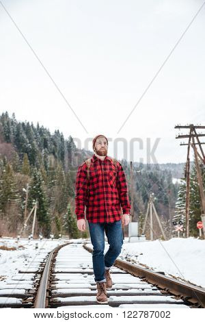 Male hiker walking on railway near forest