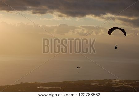 View of Paragliding backlit flying at sunset