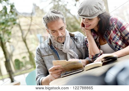 Couple of tourists in town looking at city guide