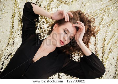Relaxed tender young woman in black dress lying on sparkling background