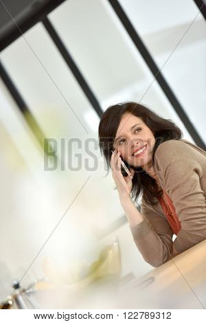 Middle-aged woman in kitchen talking on phone
