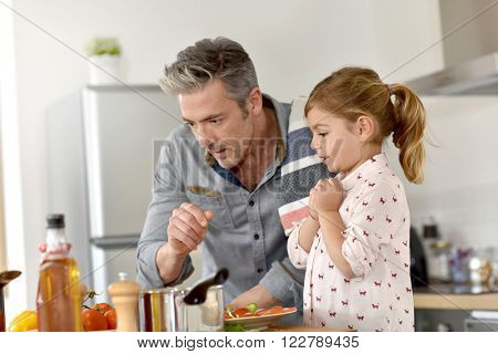 Father with little girl cooking together in kitchen