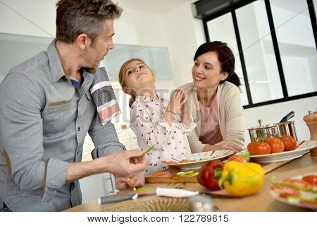 Parents with child cooking together at home