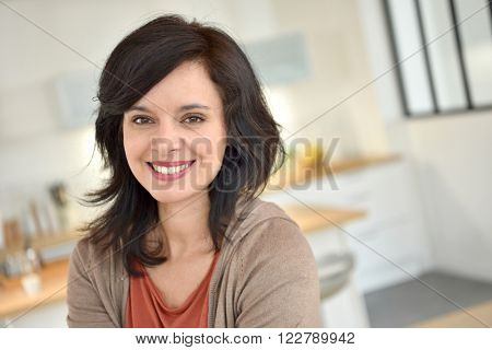 Portrait of smiling 40-year-old woman at home