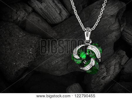 jewelry pendant witht gem on dark coal background copyspace