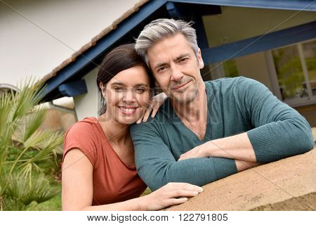 Middle-aged couple standing in front of new home