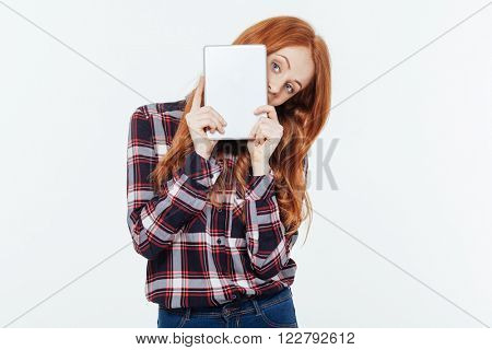 Redhead woman peeping from tablet computer isolated on a white background