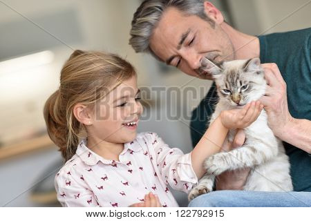 Daddy with little girl petting cat at home
