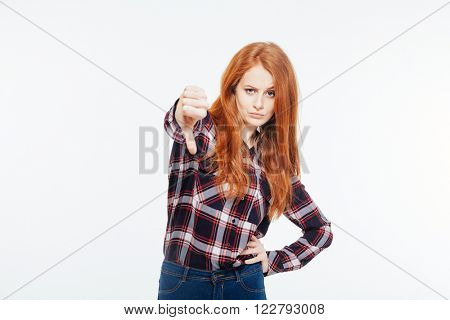 Young redhead woman showing thumb down isolated on a white background