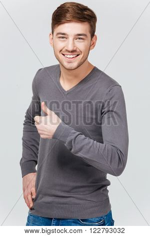 Happy handsome young man in grey pullover showing thumbs up over white background