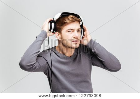 Handsome young man in grey pullover taking off headphones over white background