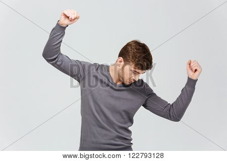 Attractive young man in grey pullover dancing over white background