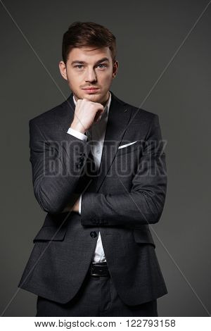 Serious attractive young businessman in black suit standing with hands folded over grey background