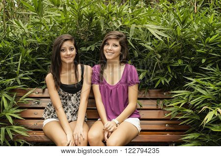 two young women sitting in a bench in a beautiful park of Houston in a summer day
