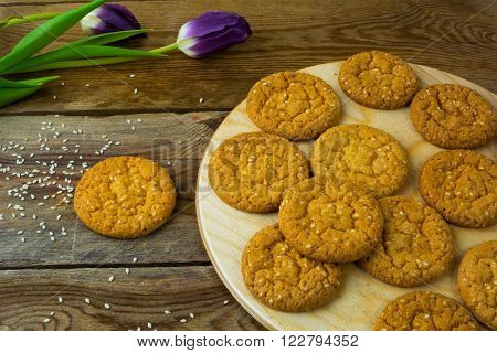 Homemade sesame cookies and two purple tulips on rustic background. Breakfast cookie. Dessert cookies. Cookies. Cookie. Dessert. Breakfast. Sweet cookie.