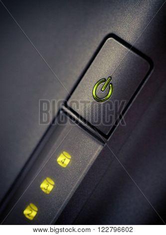 Green glowing power button Closeup shot