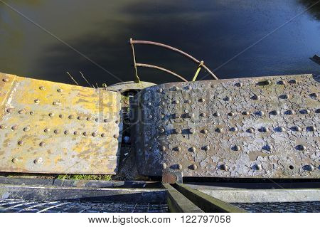 an industrial grunge metal background of an old bridge over water