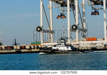 Alameda, CA - March 9, 2015: Oakland Container Shipyard, San Francisco Bay Tug boat going to meet ship coming in