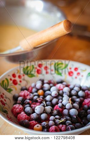 Blackcurrants and raspberries in white bowl on table