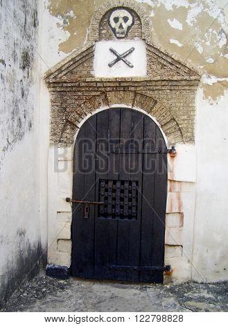 Skull and crossbones mark the door to the Men's Dungeon at Elmina Castle, Ghana, West Africa