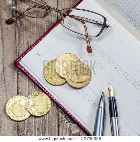 glasses pen and coins close-up notebook business still life