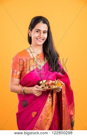 pretty Indian woman performing puja, indian girl with pooja thali or puja thali, portrait of a beautiful young lady with pooja thali, isolated over yellow background