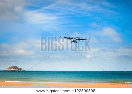 Airplane landing over the tropical lagoon at sunny day