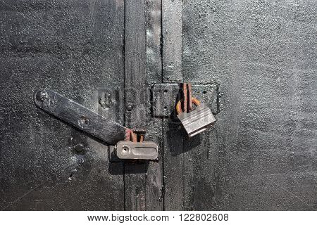 Steel lock on the rusty black metal door. close-up. focus on lock