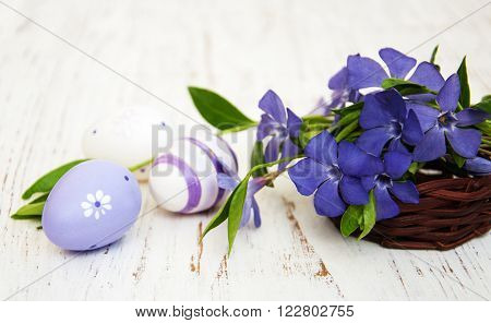 basket with beautiful blue periwinkle and easter eggs