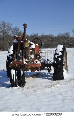 An old vintage rusty tractor is left in a cold winter snowbank