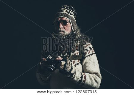 Vintage senior mountaineer holding SLR camera wearing knitted sweater and fur collar.