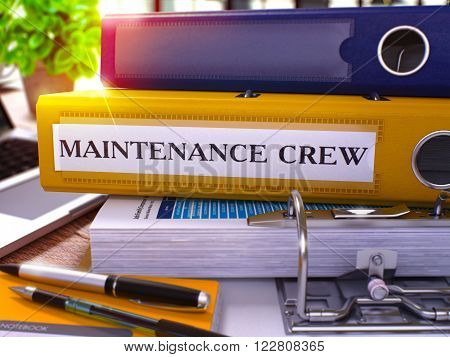 Yellow Ring Binder with Inscription Maintenance Crew on Background of Working Table with Office Supplies and Laptop. Maintenance Crew Business Concept on Blurred Background. 3D Render.