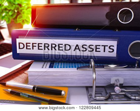 Blue Office Folder with Inscription Deferred Assets on Office Desktop with Office Supplies and Modern Laptop. Deferred Assets Business Concept on Blurred Background. Deferred Assets - Toned Image. 3D.