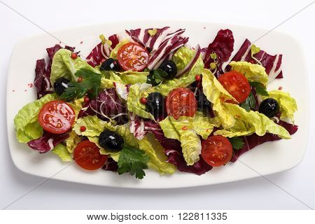 Salad with radicchio lettuce tomatoes and black olives.