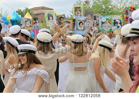 STOCKHOLM SWEDEN - JUN 10 2015: Group of happy teenages wearing graduation caps funny posters in the background celebrating the graduation after finishing high school at the school Globala gymnasiet June 10 2015 Stockholm Sweden