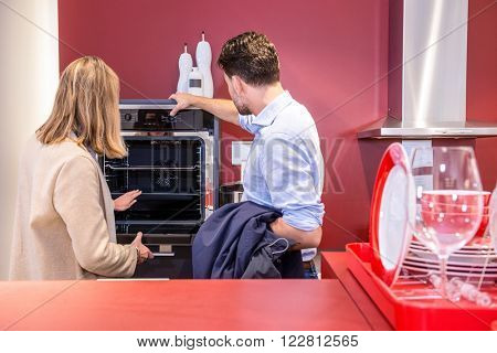 Young couple choosing microwave in household appliance section at hypermarket